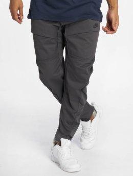 Nike tepláky Sportswear Tech Pack šedá