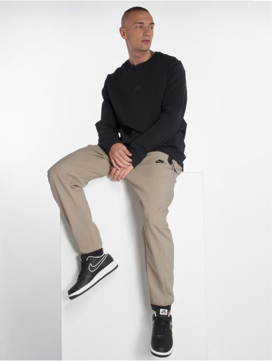 Nike tepláky Sportswear Tech Pack béžová